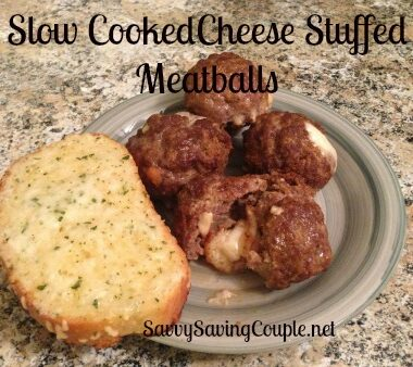 Cheese stuffed meatballs with a slice of garlic bread on a green plate.