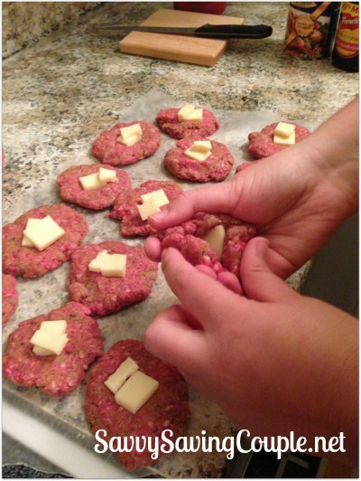 A white hand rolling up cheese-stuffed meatballs on a kitchen counter.