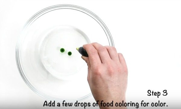 adding drops of green food coloring to clear glue in mixing bowl.