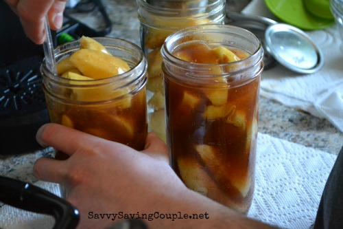 A man's hand holding a jar while canning apple pie filling.