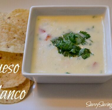 A white, rectangular dish with cilantro-topped queso and a side of chips.