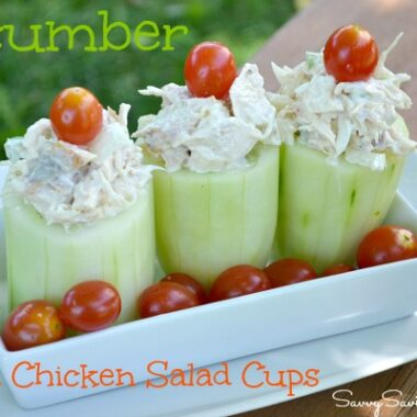 Green cucumber cups stuffed with grilled chicken salad and topped with a cherry tomato.