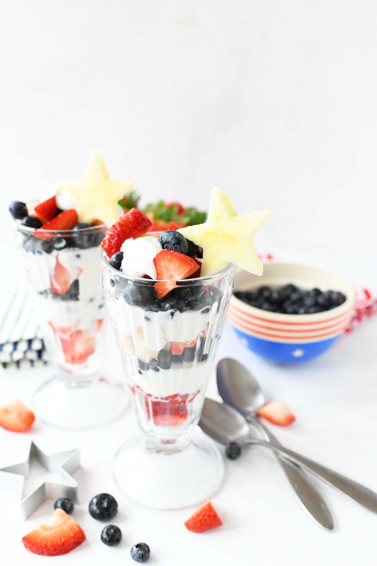 Patriotic Fruit Parfaits with berries, and apple star toppers.