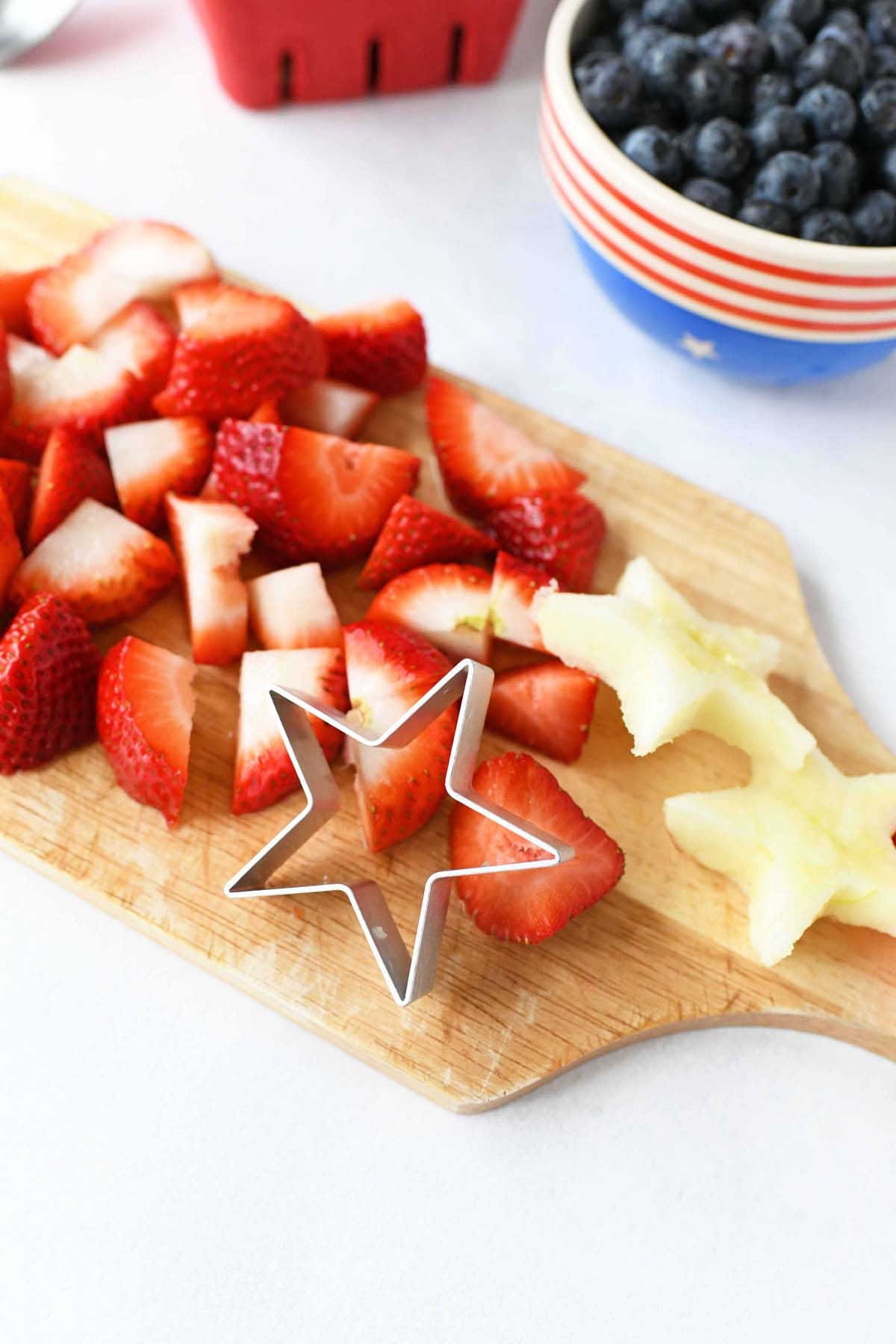 Sliced strawberries and star apple cutouts on a wooden cutting board.