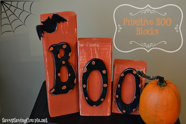 Orange wooden Halloween Blocks that spell out Boo near a pumpkin.