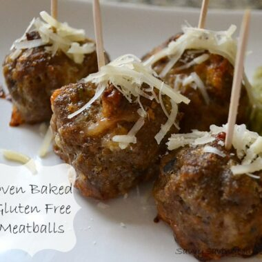 Juicy meatballs with cheese and a toothpick in them on a white plate.