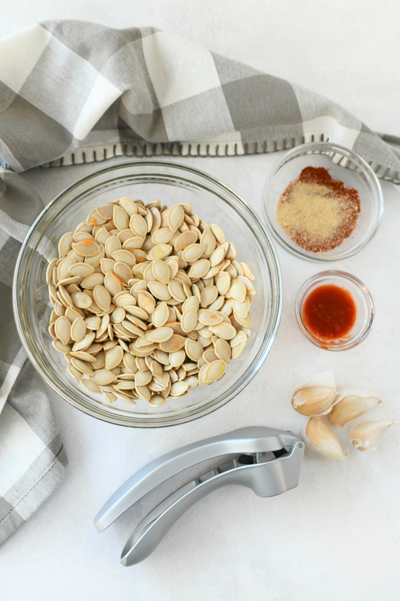 Portuguese Pumpkin Seeds ingredients on a white table with a checkered grey napkin.