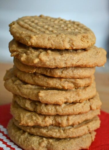 9 peanut butter cookies stacked on a red and white napkin.