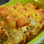 Cheesy tater tot breakfast casserole on a red spatula.