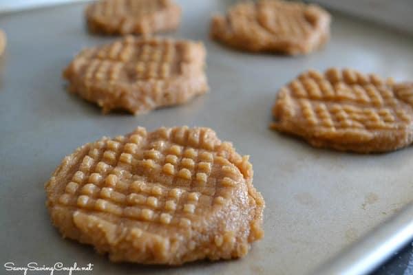 Raw, cross-hatch peanut butter cookies on a baking sheet.