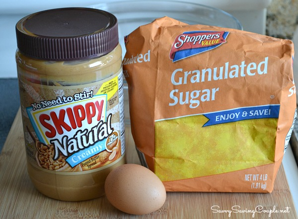A jar of peanut butter, an egg, and a bag of sugar on a wooden cutting board.