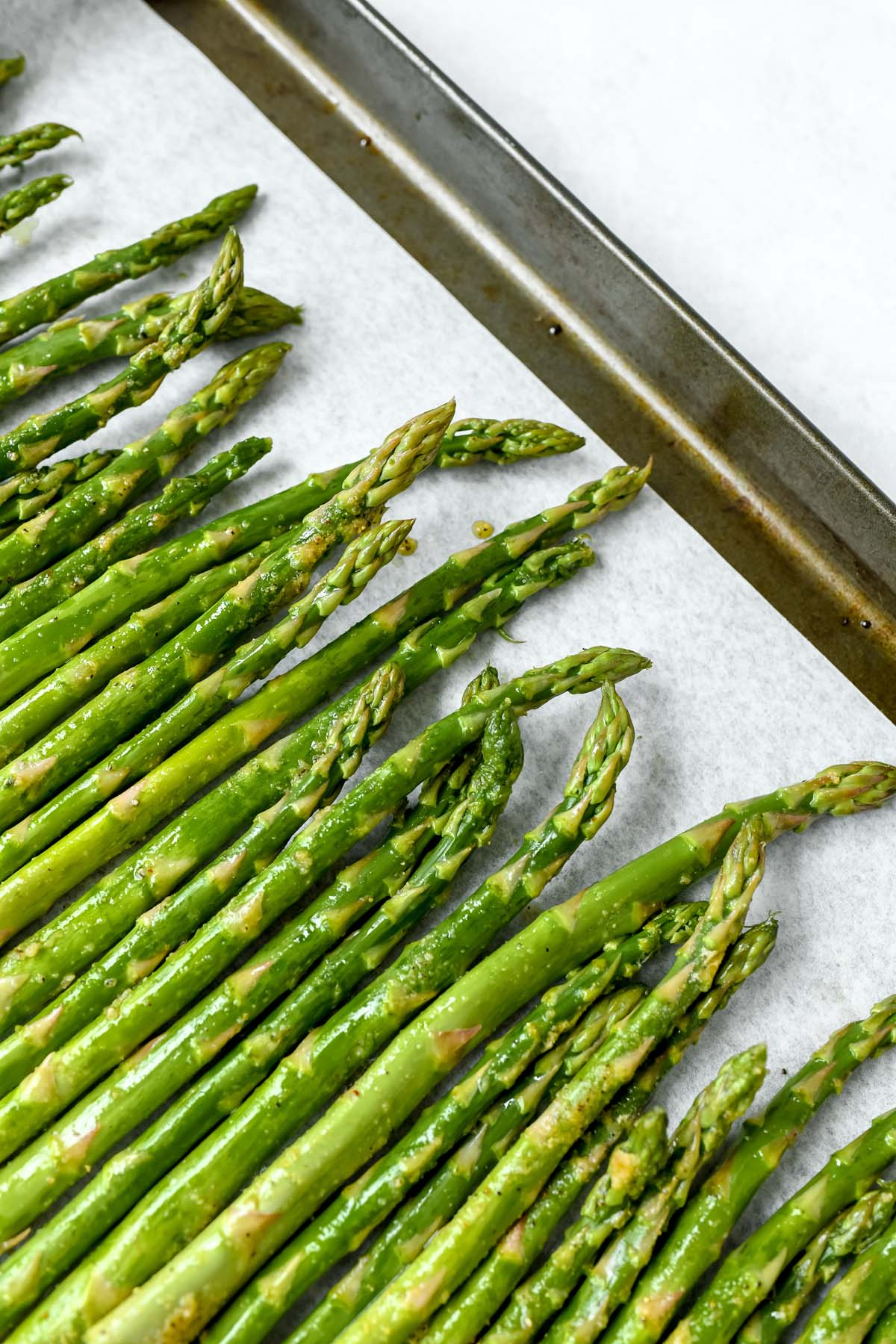 Raw stalks of asparagus on a parchment-lined baking sheet.
