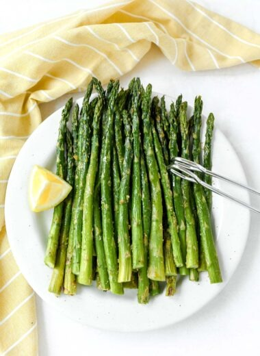 Oven roasted asparagus baked with lemon on a white plate with tongs.