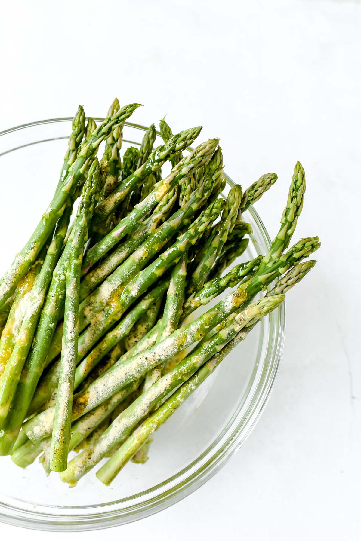 Spiced and oiled asparagus in a glass bowl.