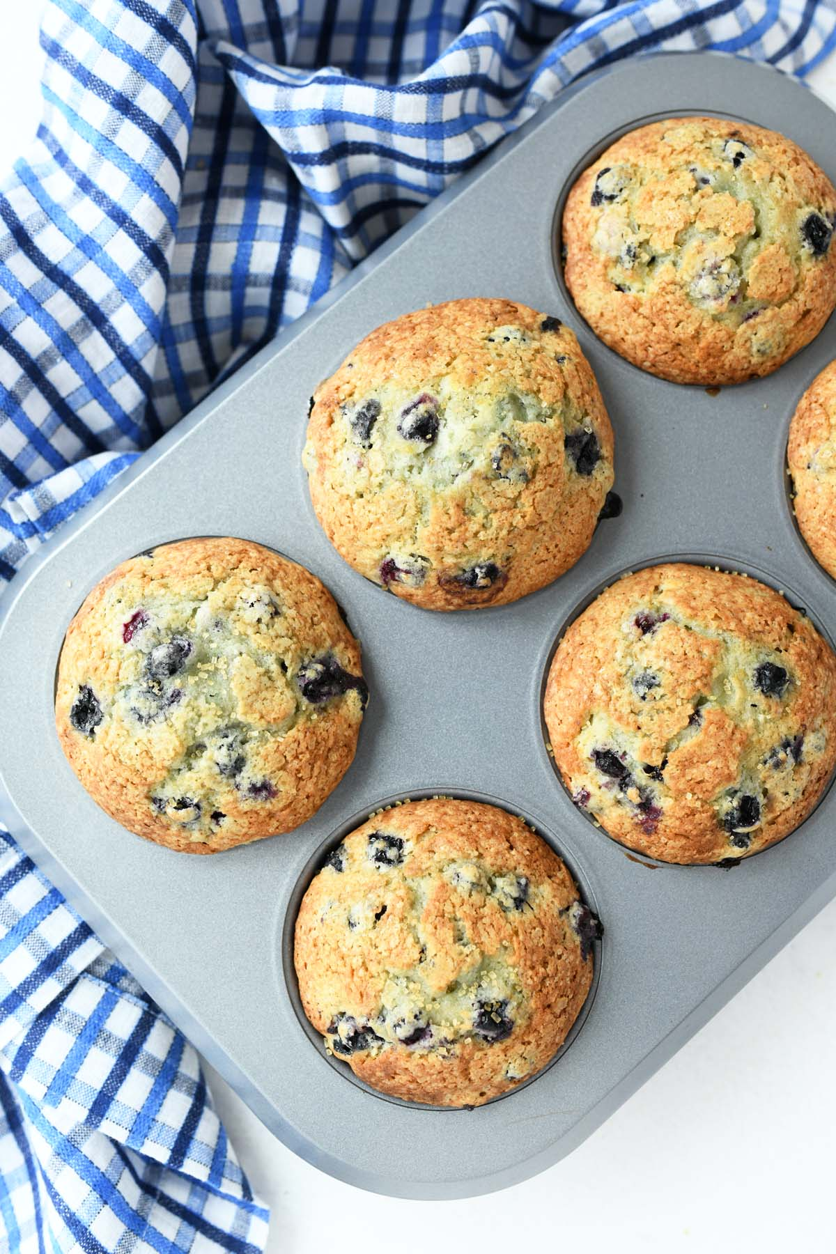 Jumbo Blueberry Muffins in a silver muffin tin with a blue plaid napkin.