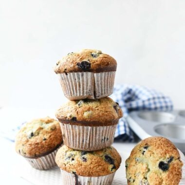 Jumbo Bakery Style Blueberry Muffins stacked on a white table.