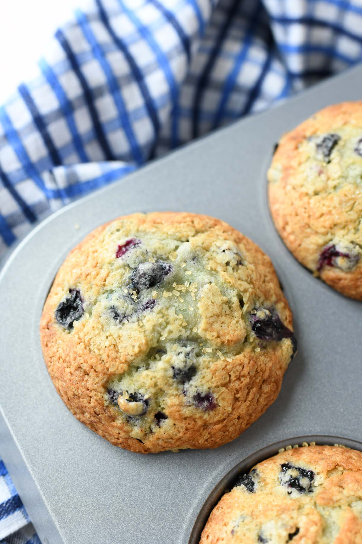 Jumbo blueberry muffin in a silver tin with a blueberry napkin.