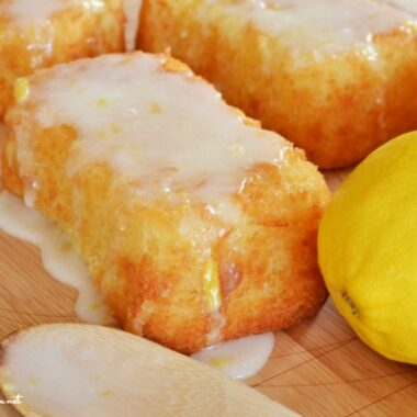 Mini iced lemon loaf with a fresh lemon nearby.