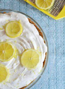 No Bake Lemon Cream Pie with virbrant yellow lemon slices and zest on top.