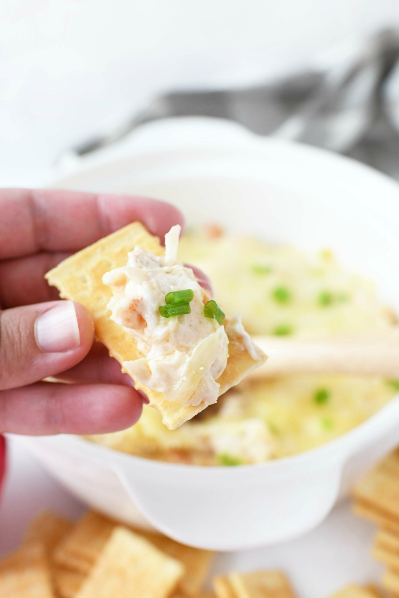 Crab Rangoon Dip recipe on a cracker in someones hand.