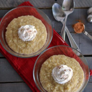 cinnamon vanilla rice pudding in glass dishes with whipped cream