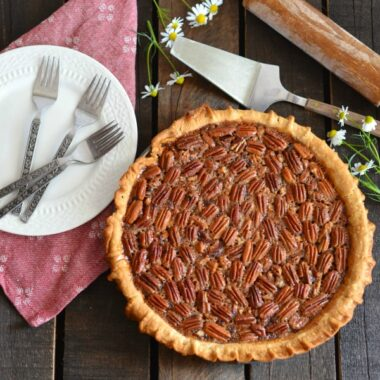 Southern Pecan Pie on a table with plates, and servingware.
