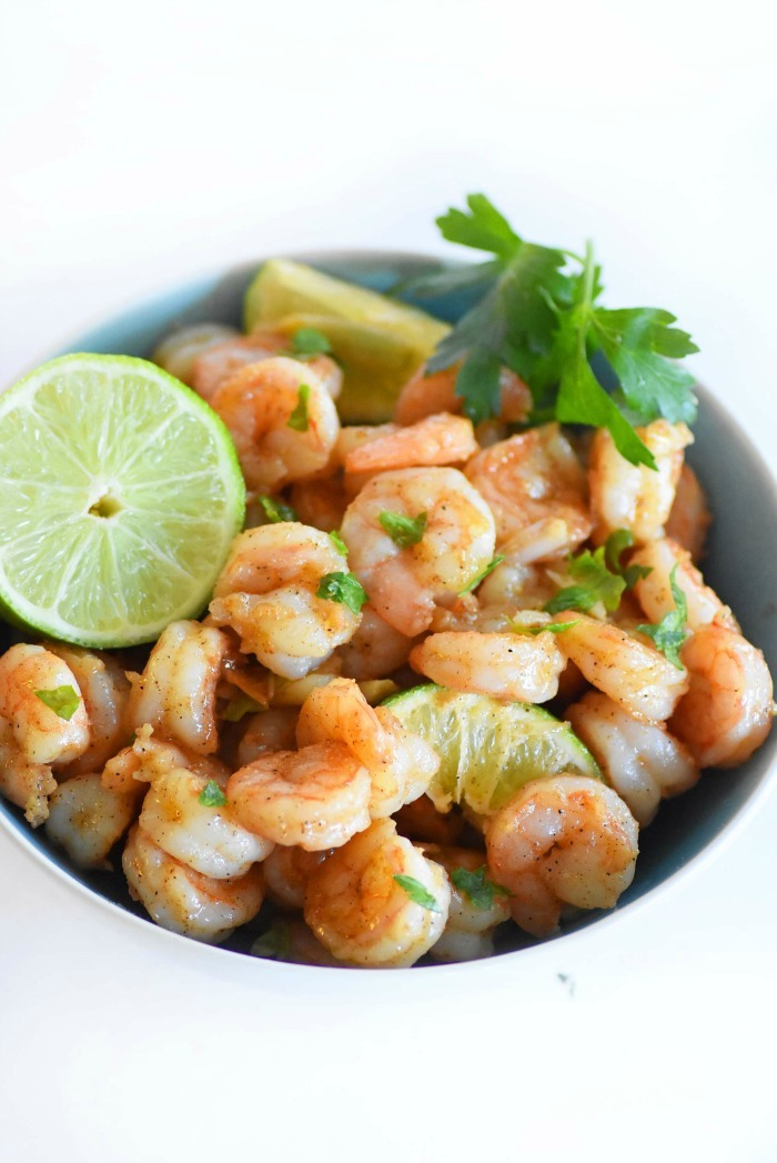 Garlic Lime shrimp in a blue bowl with a lime wedge.