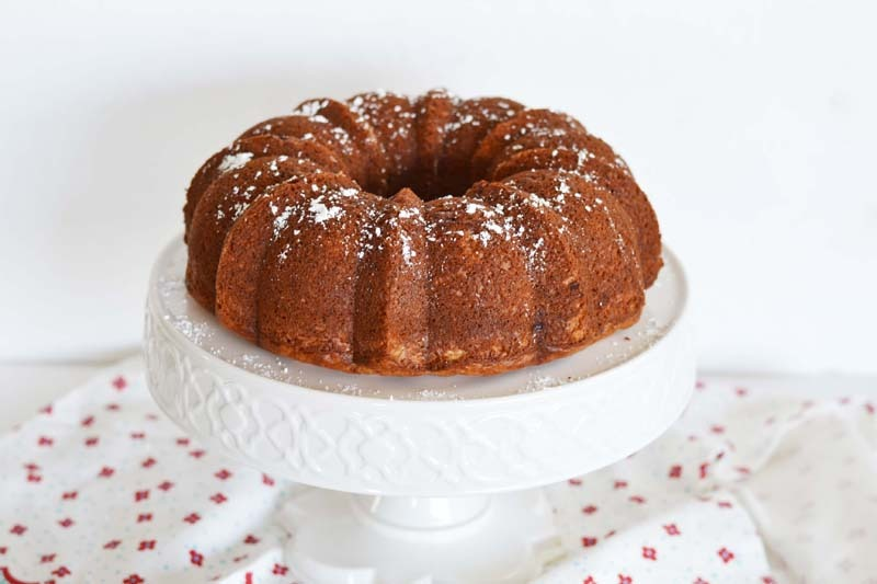 Banana Bundt Cake with Cream Cheese on a white cake stand. There is also a napkin on the table.