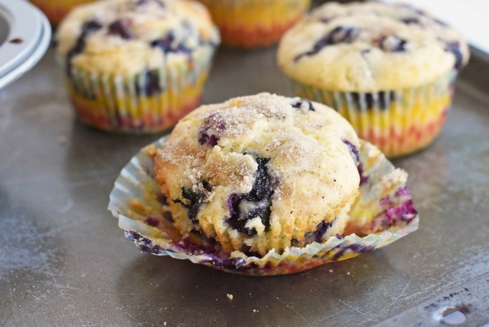 Fresh baked blueberry muffin recipe with liner half removed.