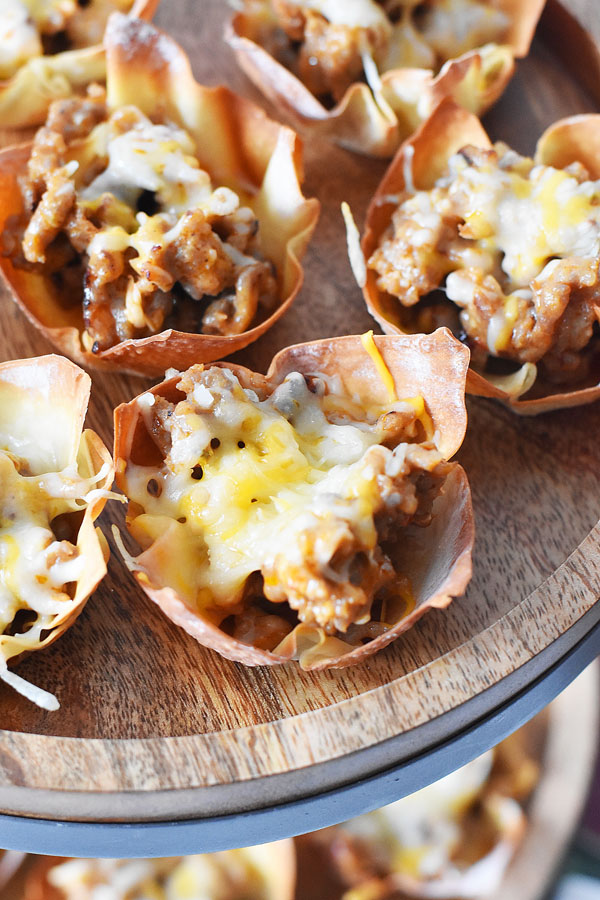 Crispy golden brown sausage and cheese baked wontons on a wooden stand.