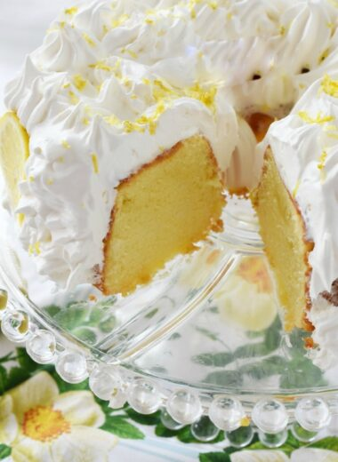 Frosted Lemon Chiffon Cake on a clear platter with a slice missing.