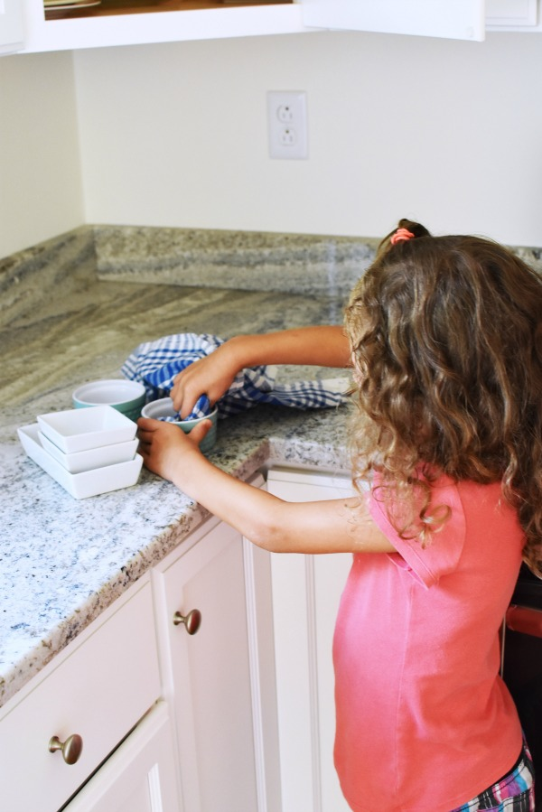 little girl putting dishes away1