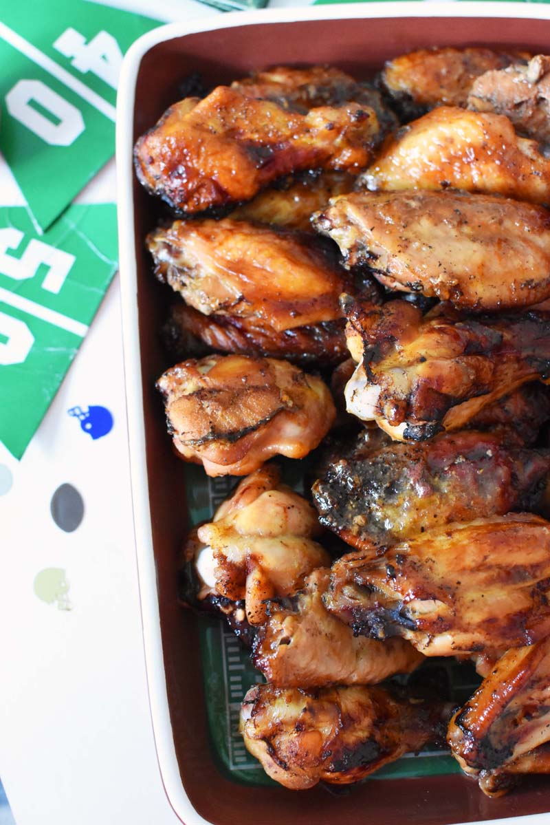 Oven Baked Dr Pepper Wings in a football themed casserole dish. There is football décor on the white table nearby.