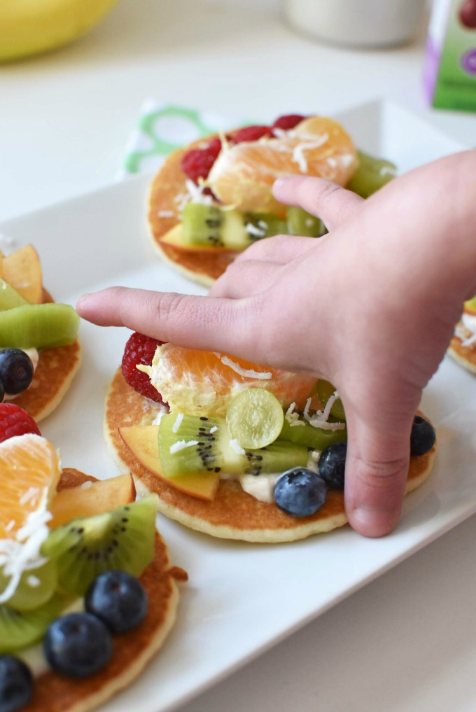 child picking up pancake fruit pizza