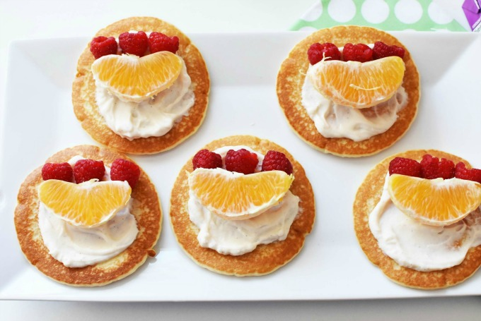 pancakes with yogurt, raspberry and orange slices