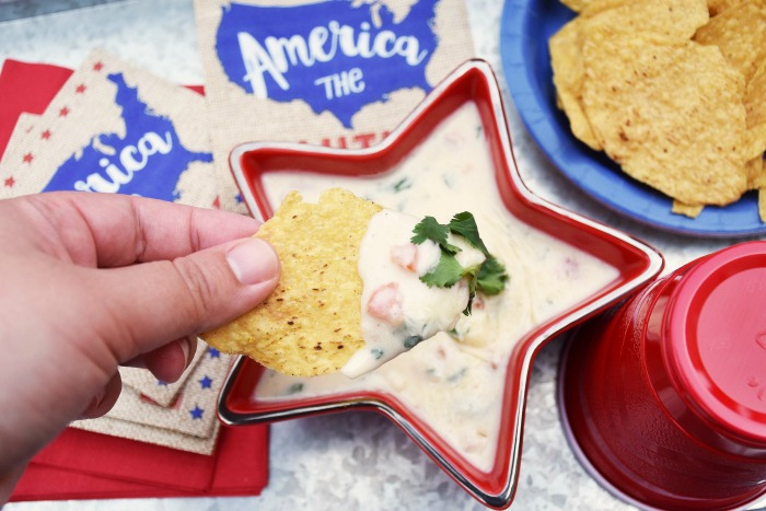 Dipping a Chip into White Queso with Tomato and Cilantro