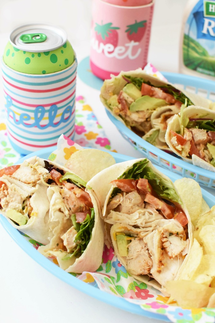 Grilled Chicken Salad Wraps in a blue basket with chips and drinks.