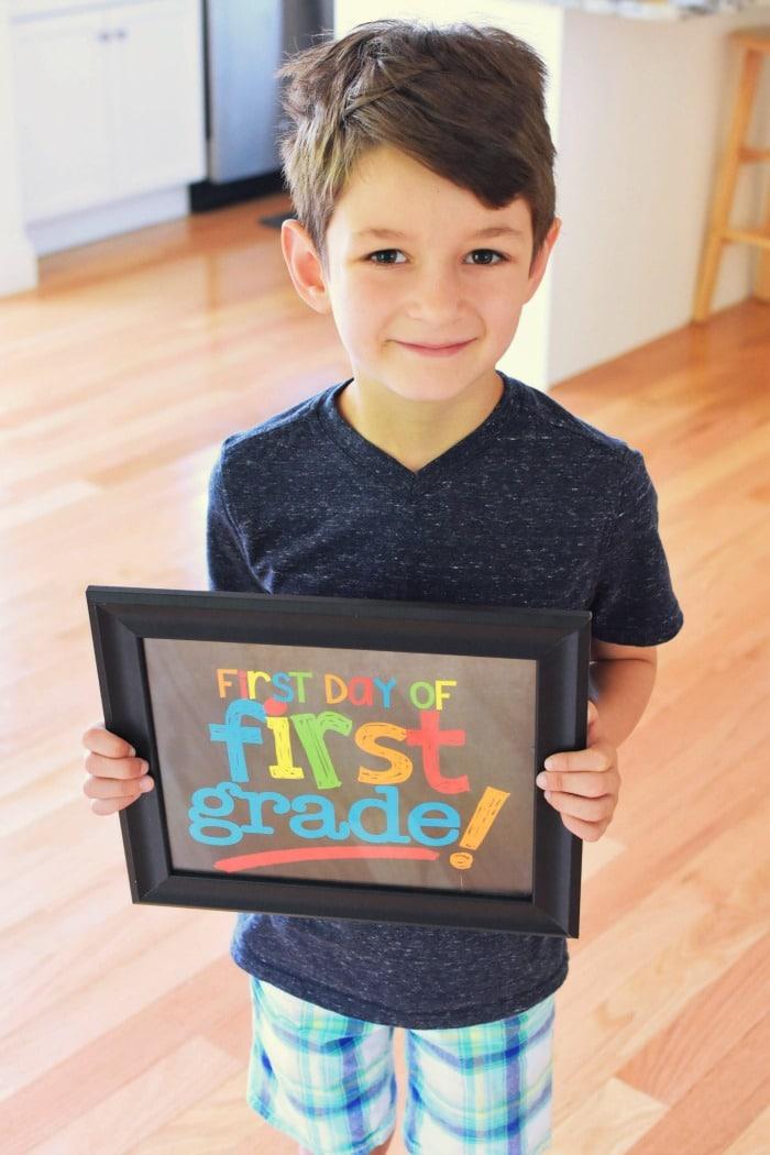 Boy holding first grade sign 1