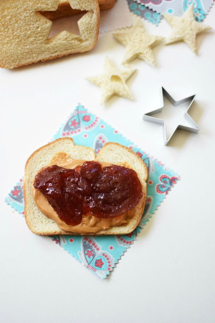 Peanut Butter and Jelly on sliced bread with a star cutout on the white table.