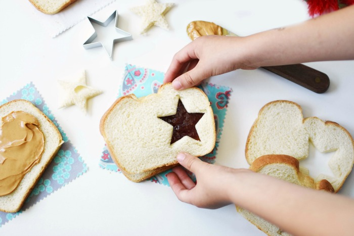 Peanut Butter and Jelly Star Sandwich with a child touching the bread.