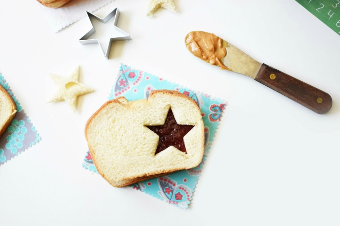Star cut out Peanut Butter and Jam sandwich with a knife with peanut butter on it.