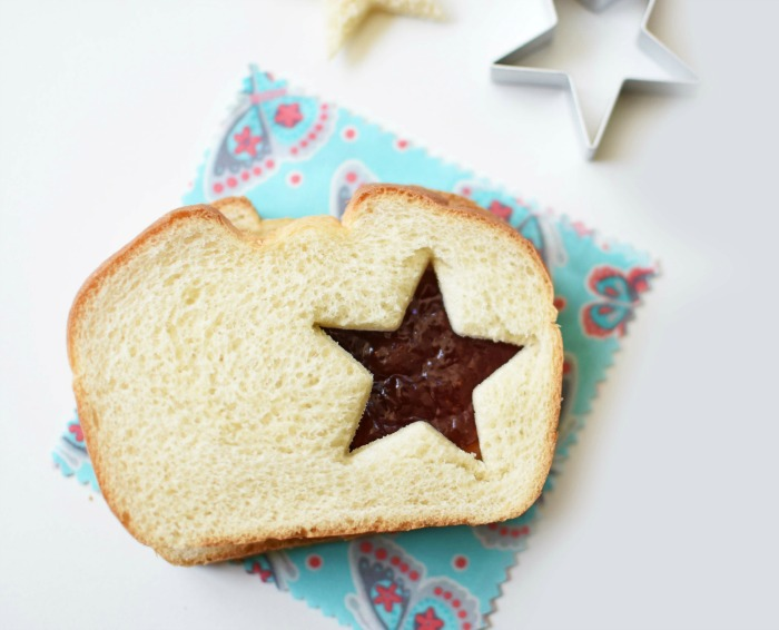 Peanut Butter and Jelly Star Sandwich Cutout on a blue printed napkin.