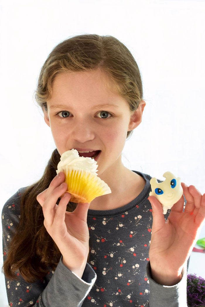 Girl eating light fury vanilla cupcake