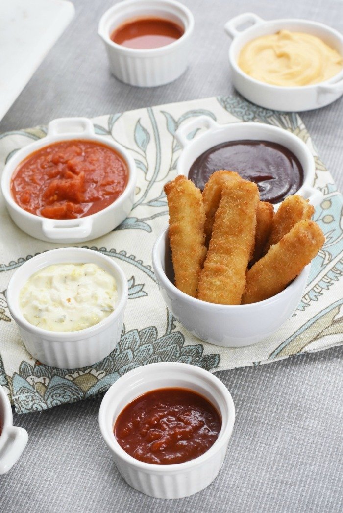 Fish Sticks in white dish with dipping sauces.