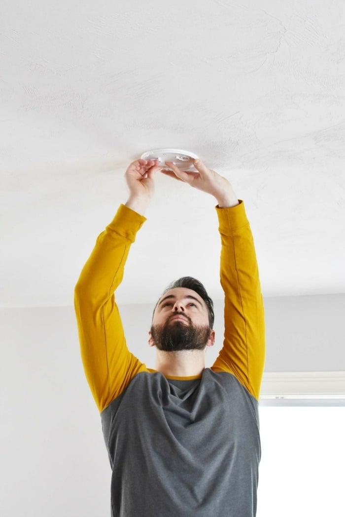 man installing a fire alarm