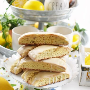 Lemon Almond Biscotti stacked on a white cake stand.