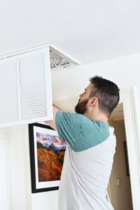 Man putting clean air filter in 1