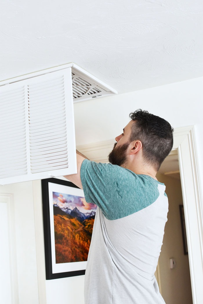 man changing home air filter in ceiling