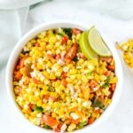 Colorful corn salad in a white bowl with lime wedges.