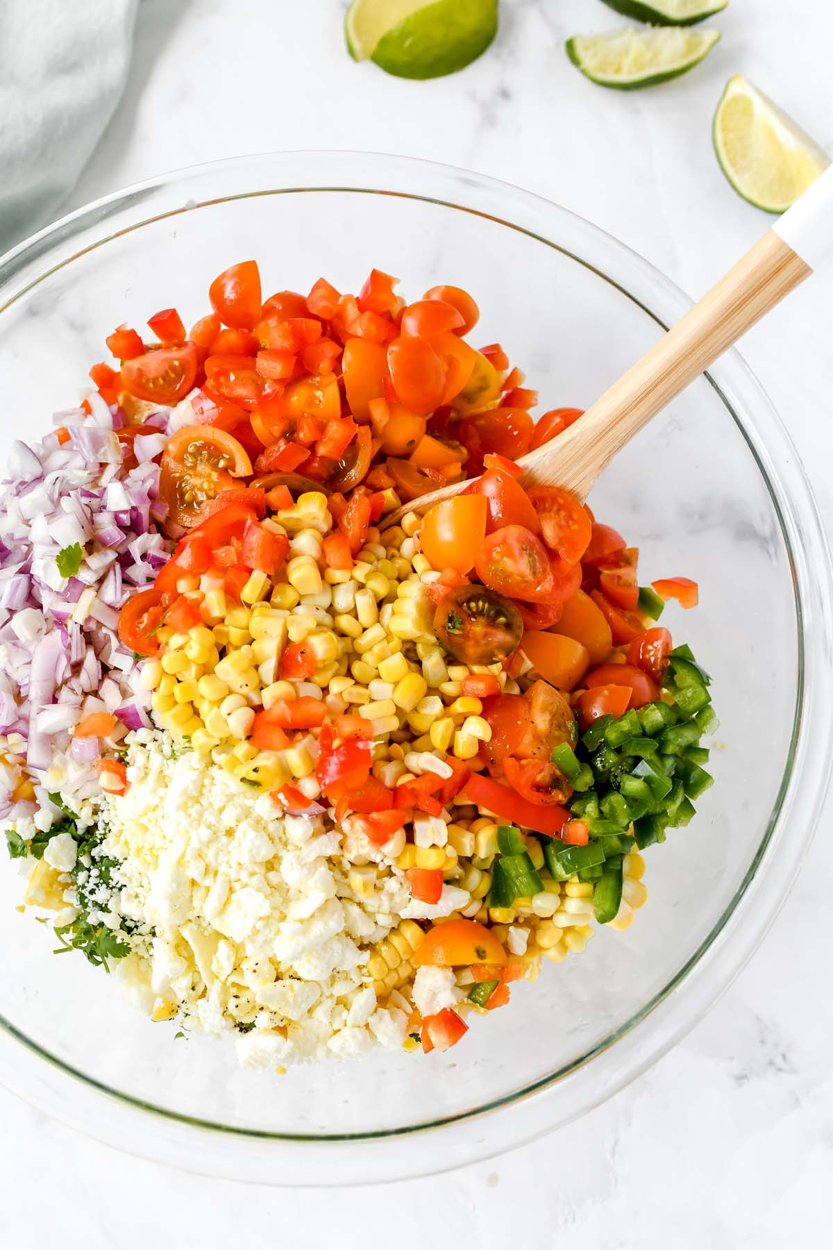 Colorful corn salad ingredients in a large glass bowl.